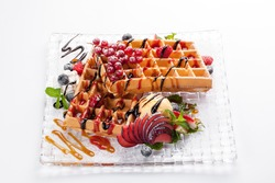 soft Belgian waffles with ice cream and forest berries and mint, strawberries, blackberries, raspberries and red currants, lie on a square glass plate on white background