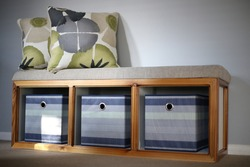 Soft bench with three storage spots. Wooden frame with gray fabric top and white sides.