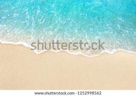 Soft blue ocean wave on clean sandy beach #1252998562
