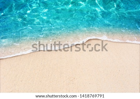 Photo of  Soft blue ocean wave on clean sandy beach