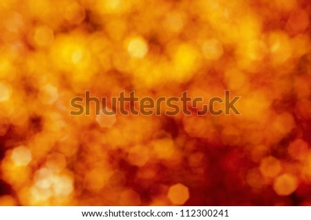 Soft, blurry, photographed bokeh background of reds and yellows, giving a fire-like, explosive effect.