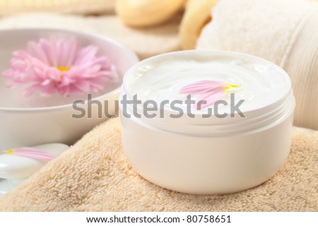 Soft body, hand and face cream with pink petals on top in a bathroom/spa setting (Selective Focus, Focus on the horizontal/back petal on the cream)