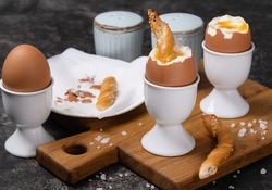 Soft-boiled chicken egg for breakfast with toast on black background