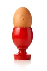 soft-boiled egg served on red wooden egg cup isolated in total white background