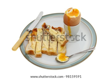 Soft boiled egg, toast soldiers a spoon and knife on a plate isolated against white