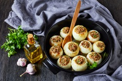 Soft, caramelized, oven-baked onions stuffed with minced lamb and rice in a black ceramic baking dish on a dark wooden table, horizontal view from above