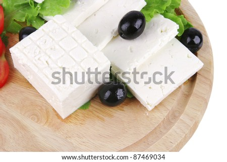 soft cheese with olives on wooden plate