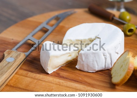 Soft cheese with white rind (camembert or brie) on wooden board with roasted bread slices. Cheese knife also included
