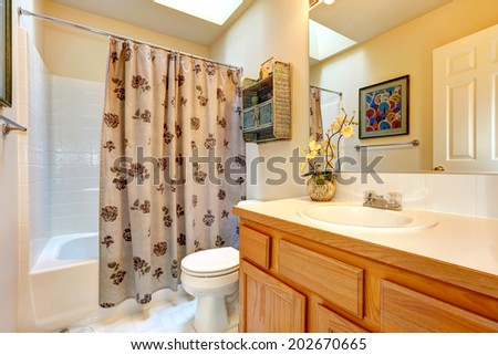 Soft colors bathroom with honey tone bathroom vanity cabinet, large mirror. View of bath rub with curtains #202670665