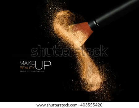 Soft cosmetics brush releasing a cloud of glowing sparkling face powder over a black background with copy space in a beauty and makeup concept