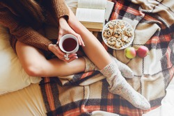 Soft cozy photo of slim tan woman in warm sweater on the bed with cup of tea in hands, top view point. Girl sitting on checkered plaid near old books and cookies.