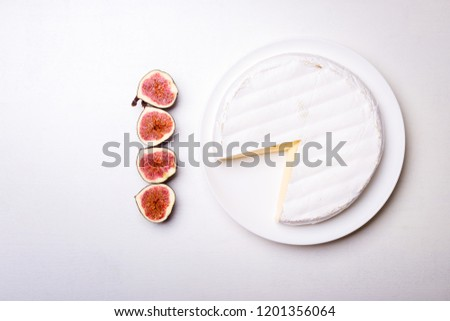 Soft creamy brie cheese with cut in half figs on white wooden background. Concept menu background
