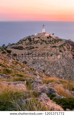 soft dreamy purple pink morning dawn sunrise vertical pic of cap de formentor light house on dry rocky sand cliff with yellow dry grass wavy road with sea ocean on background. Mallorca Majorca Spain