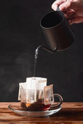 Soft Drink : a mug of coffee / a hand with black dripping pot pouring boiled hot water to coffee dripper on wooden table and black background at home with copy space