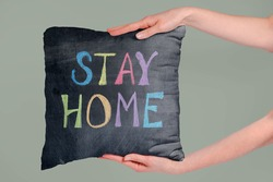 Soft fabric pillow holding by hand with stay home text