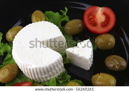 soft feta cheese on black dish with gold olives