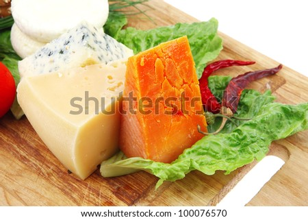 soft feta cheese with aged delicatessen cheeses on cutting wooden plate with tomatoes bread and olive oil isolated over white background - stock photo