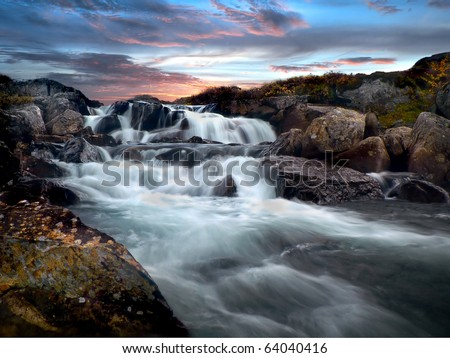 Soft floating norwegian mountain cascade river surrounded by stones with colorful clouds in the background during sunset hours