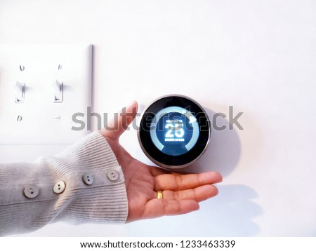 Soft focus - A women hand adjusting the temperature on modern circle thermostat, Programmable Nest Thermostat - Wireless Learning in white blurred background