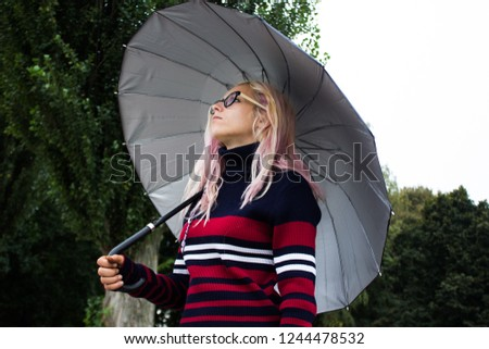 soft focus adult girl stay under umbrella in gray rainy foggy autumn day and looking up side ways, copy space