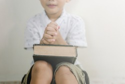Soft focus Asian boy praying in the morning with sunlight,Hands on the bible.
