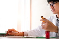 Soft focus. Asian doctor writing prescription for patient in hospital room. Pharmacist doctor prescribing drug / medication to patient. Medical treatment & health care insurance concept. Copy space.