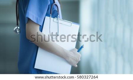 Soft focus Asian medical female doctor or nurse holding patient medical chart.