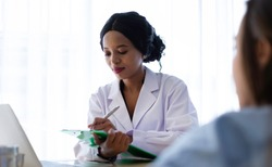 Soft focus. Black African doctor talking to recovering patient in hospital. Recovering patient consulting with doctor about medical treatment & coronavirus. Insurance & recovering patient concept.