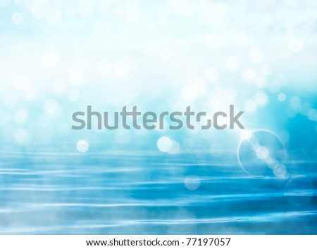 Soft focus bokeh light effects over a rippled, blue water background with  lens flare. #77197057