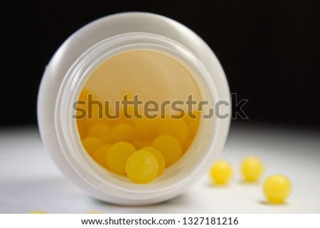 Soft focus close up of an open white bottle with yellow pills laying on its side with black background #1327181216