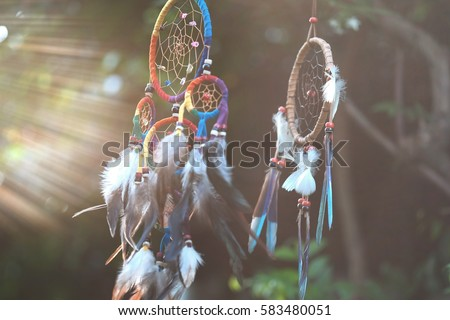 Soft focus Dream Catcher with a flare from the sun set on the background bokeh nature. Native american dream catcher. (Vintage style) boho chic, ethnic amulet. #583480051