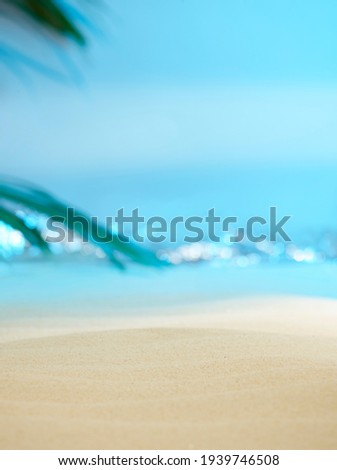Soft focus, dreamy, sandy beach with palm tree leaf and sparkling waves