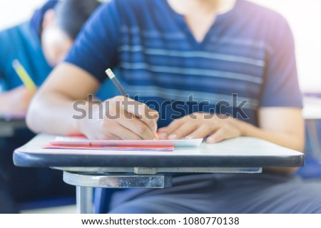 soft focus.hand high school or university student in casual holding pencil writing on paper answer sheet.sitting on lecture chair taking final exam attending in examination room or classroom.