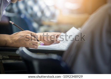 soft focus.hand high school or university student in uniform holding pencil writing on paper answer sheet.sitting on lecture chair taking final exam or study attending in examination room or classroom #1092348929