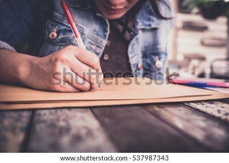soft focus hands of a young woman as she is writing letter and notepad Or something on a wooden table . Customize colors Vintage retro and old film Tone . Сток-фото ©