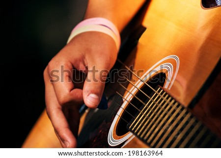 soft focus hands play on guitar, focus on string