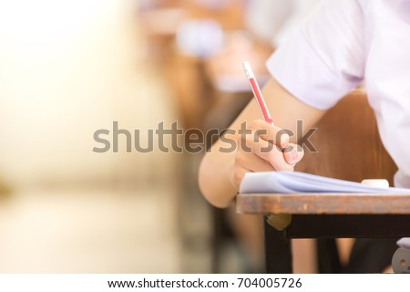 soft focus.high school or university student holding pencil writing on paper answer sheet.sitting on lecture chair doing final exam attending in examination room or classroom.student in uniform.