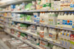 Soft focus hypermarket shelves with dairy products. Blurred background of the grocery store.
