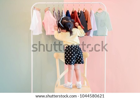 Soft Focus of a Two Years Old Child Choosing her own Dresses from Kids Cloth Rack #1044580621
