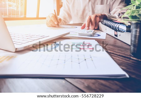 soft focus of businessman hand working laptop on wooden desk in office in morning light. vintage effect #556728229