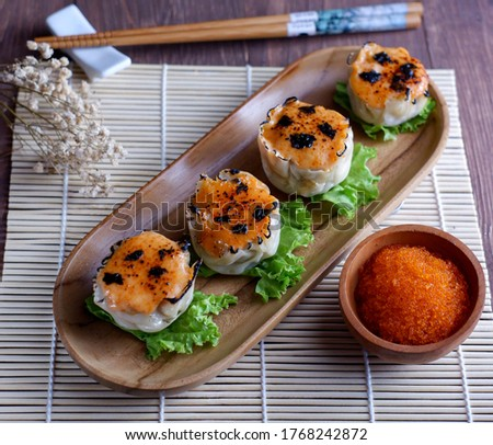 Soft focus of Dimsum Mentai Sauce. Served on the wooden tray and chopstick. Dimsum is the cuisine from Tiongkok. Its famous at all country. Photo stock ©