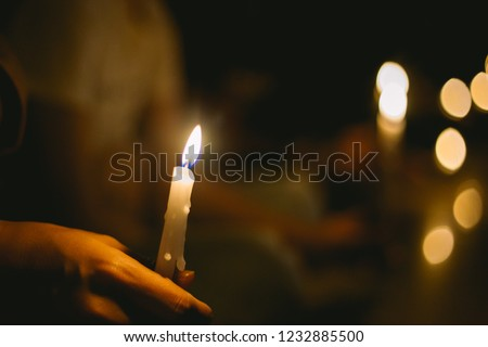 Photo of  soft focus of people lighting candle vigil in darkness seeking hope, worship, prayer