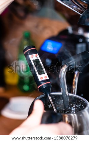 soft focus of soft focus of barista hands measure hot water temperature with in silver jug in cafe