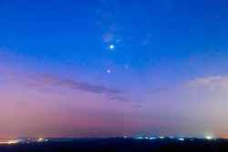 Soft focus of Venus, Jupiter and Scorpius In the sky near the morning with light from the city in the valley below.