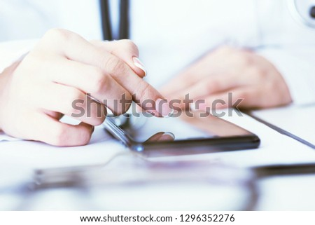 Soft focus of woman doctor touching screen on modern smart phone during the consultation in the workplace hospital. #1296352276