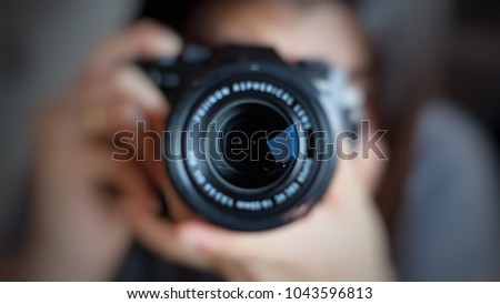 Soft focus of women photographer hold camera and taking a photo.  #1043596813