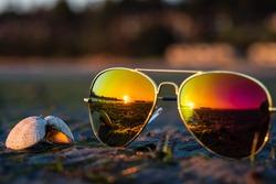 Soft focus on aviator sunglasses & seashell with reflection of beautiful colorful sunrise in horizon