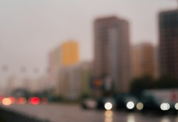 Soft focus or defocused urban photo. Autumn cloudy and misty evening. Blurred cityscape background. Defocused city buildings and highway traffic.Long exposure.