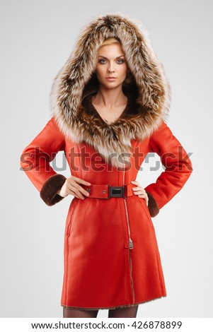 Stock Photo Soft focus portrait of attractive lady in red sheepskin coat posing with fur hood on her head