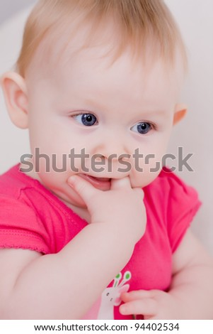 Soft focus portrait of beautiful little baby girl touching her teeth